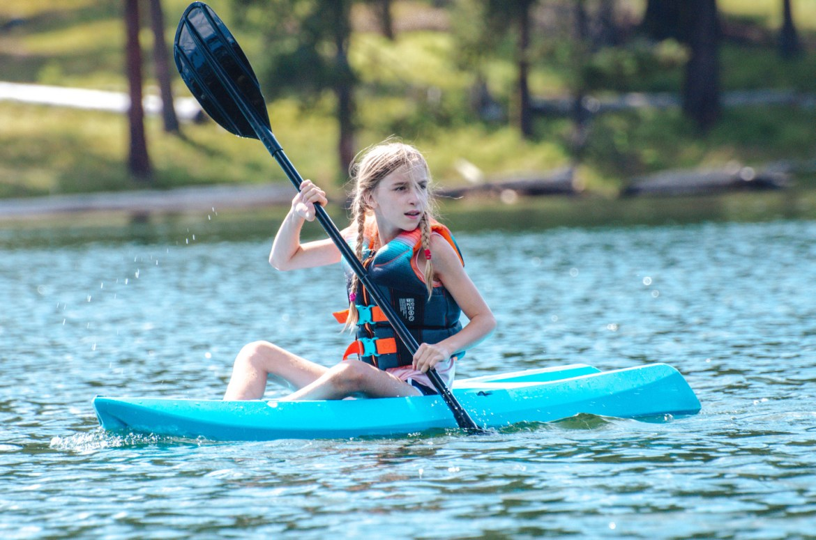 Best Place to Kayak - Magone Lake in Oregon.  A young girl paddles her blue youth kayak through the calm waters of Oregon's Magone Lake, near John Day, Oregon.
