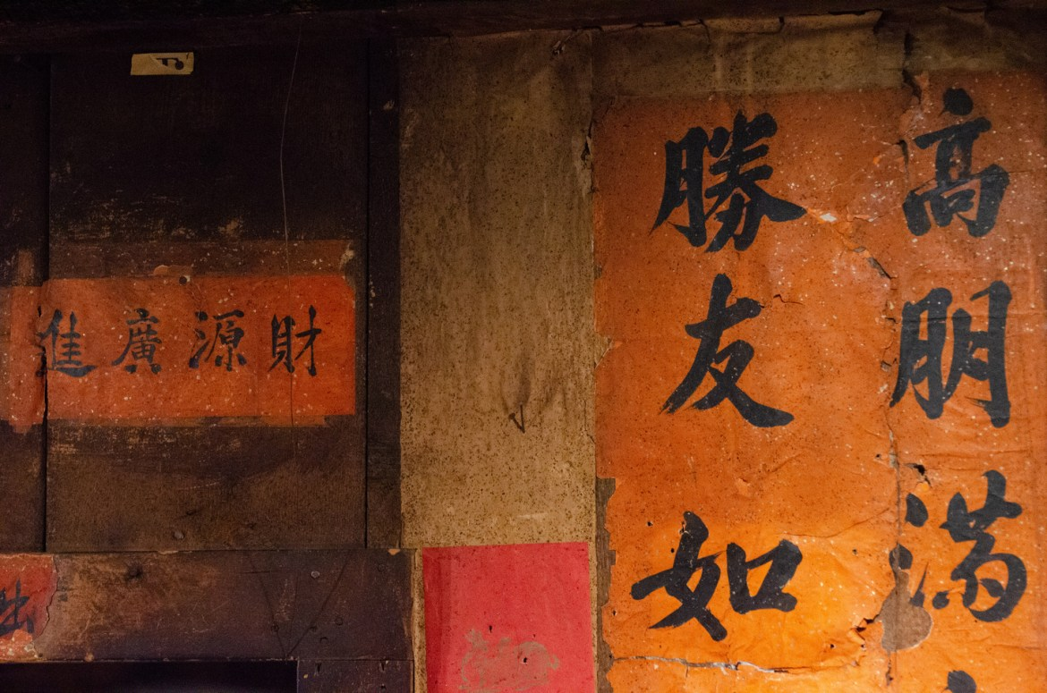 Interesting Oregon Facts: An interior view of John Day, Oregon's Kam Wah Chung & Company, the most significant collection of 19th and 20th Century artifacts documenting Chinese immigrants in the American West.  This image shows Mandarin Chinese writing on posters attached to the walls above and beside a door frame on orange and red paper.