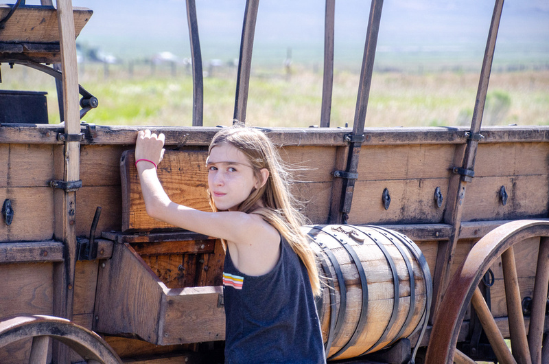 A young state park visitor inspects a  covered wagon at the visitor center in Almo, Idaho.
