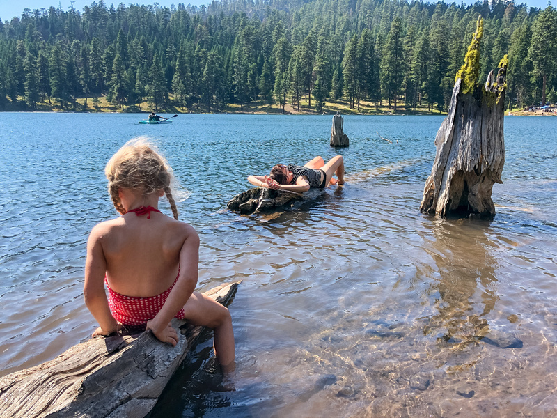 A young girl and her mother recline on sunken logs on the eastern shore of Oregon's Magone Lake, near John Day, Oregon.