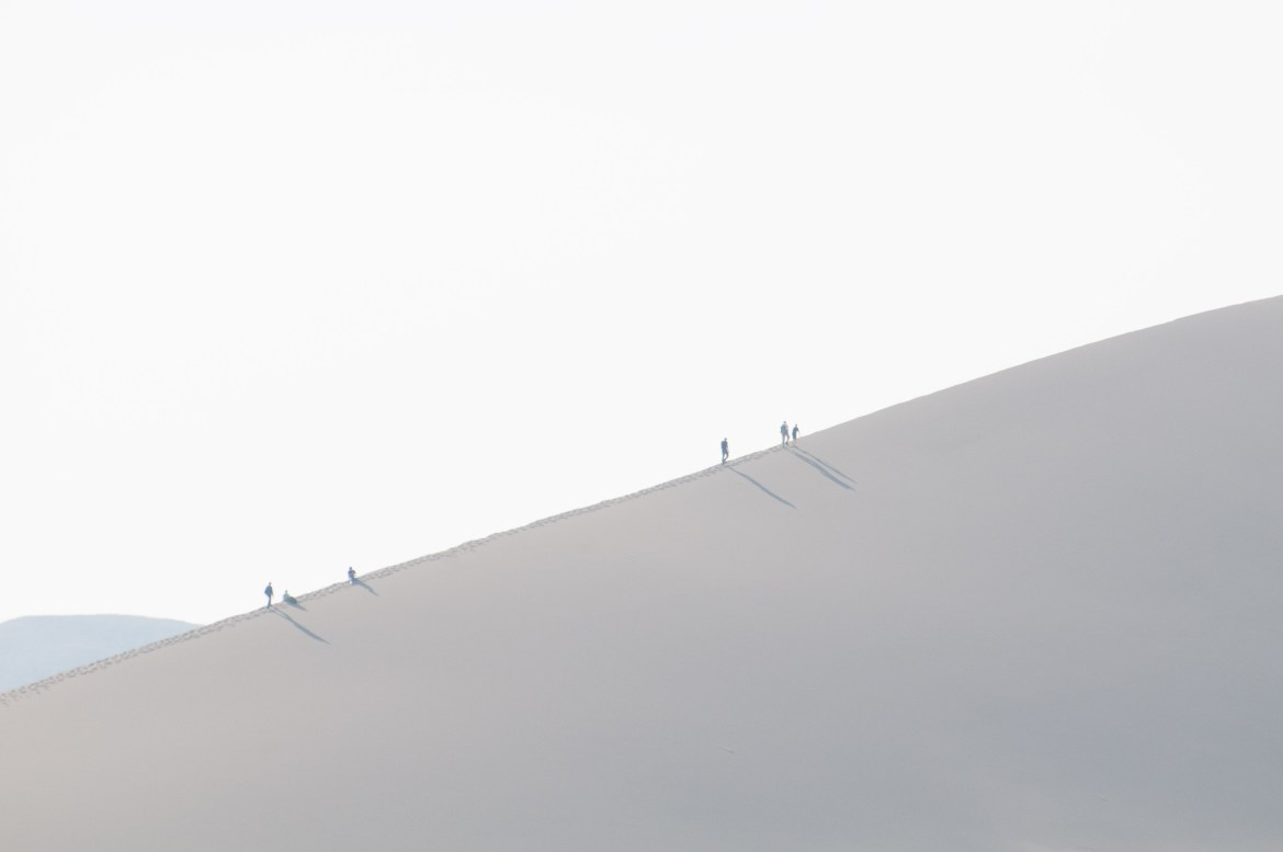 Silhouetted individuals climb sand dunes at Southwest Idaho's Bruneau Sand Dunes State Park. The dunes are the largest free-standing sand dunes in North America.
