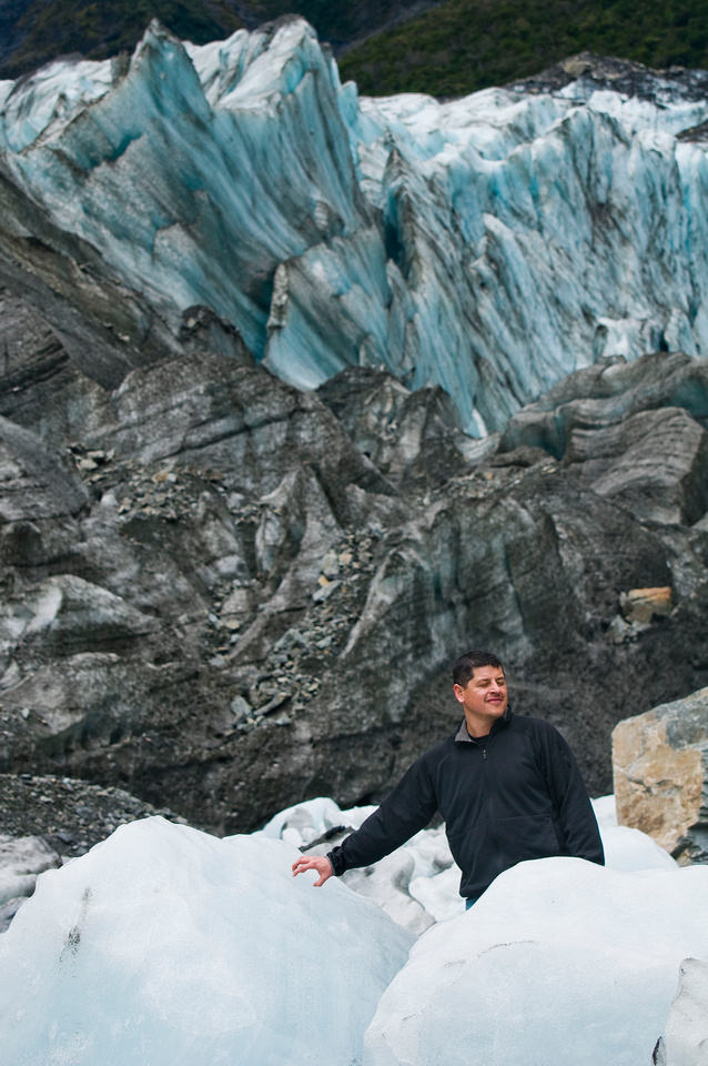 Tour New Zealand - South Island Itinerary: Fox Glacier. A man stands at the base of Fox Glacier in 2009, with large spires of blue ice visible behind car-sized chunks of ice in the foreground.