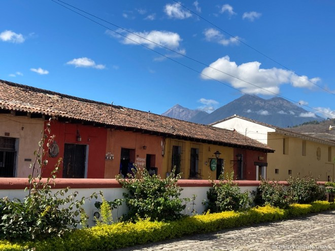 Rudy Giron: Antigua Guatemala &emdash; Vista of the Volcanoes Fuego and Acatenango looming over the rooftops of Antigua Guatemala