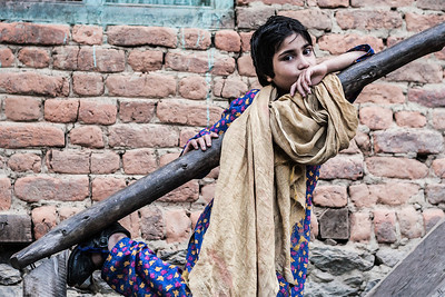 A girl wearing a blue salwar kameez and surprisingly uncovered head poses for the camera as she climbs up the steps to her house in Lolab Valley in the Kupwara district in northern Kashmir, India.