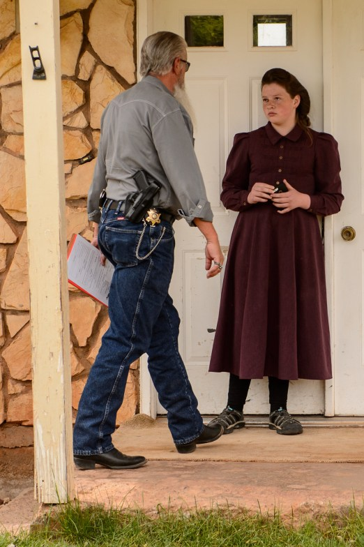 An FLDS girl stands in the doorway of a Colorado City, Ariz., home as Mohave County Constable Mike Hoggard prepares to evict her family, Tuesday May 9, 2017.