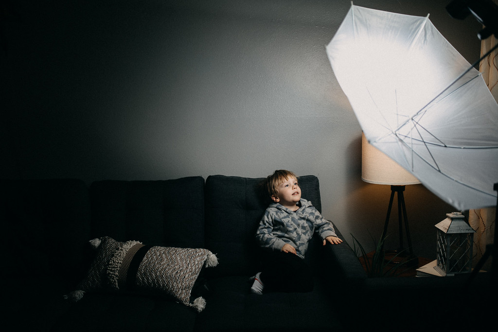 Small boy being photographed by a camera flash umbrella