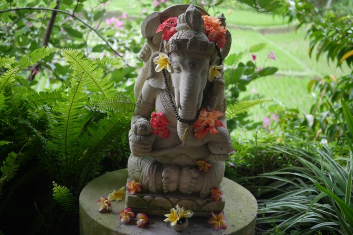 a hindu statue decorated in flowers in Ubud