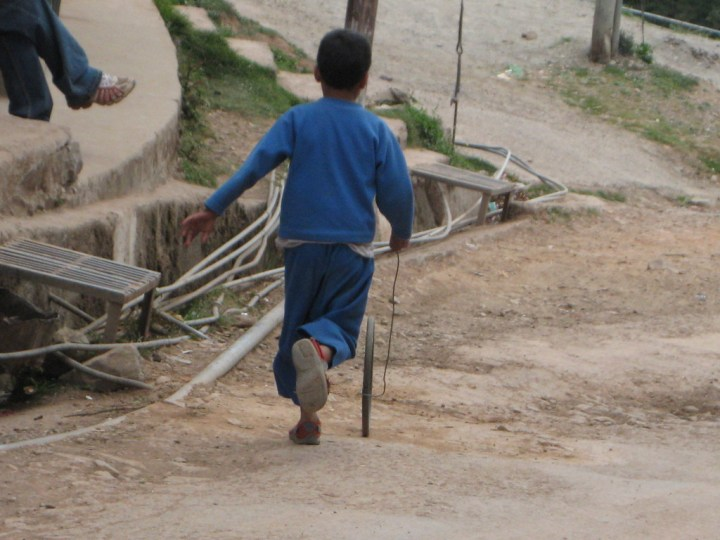 boy chasing a tire in India