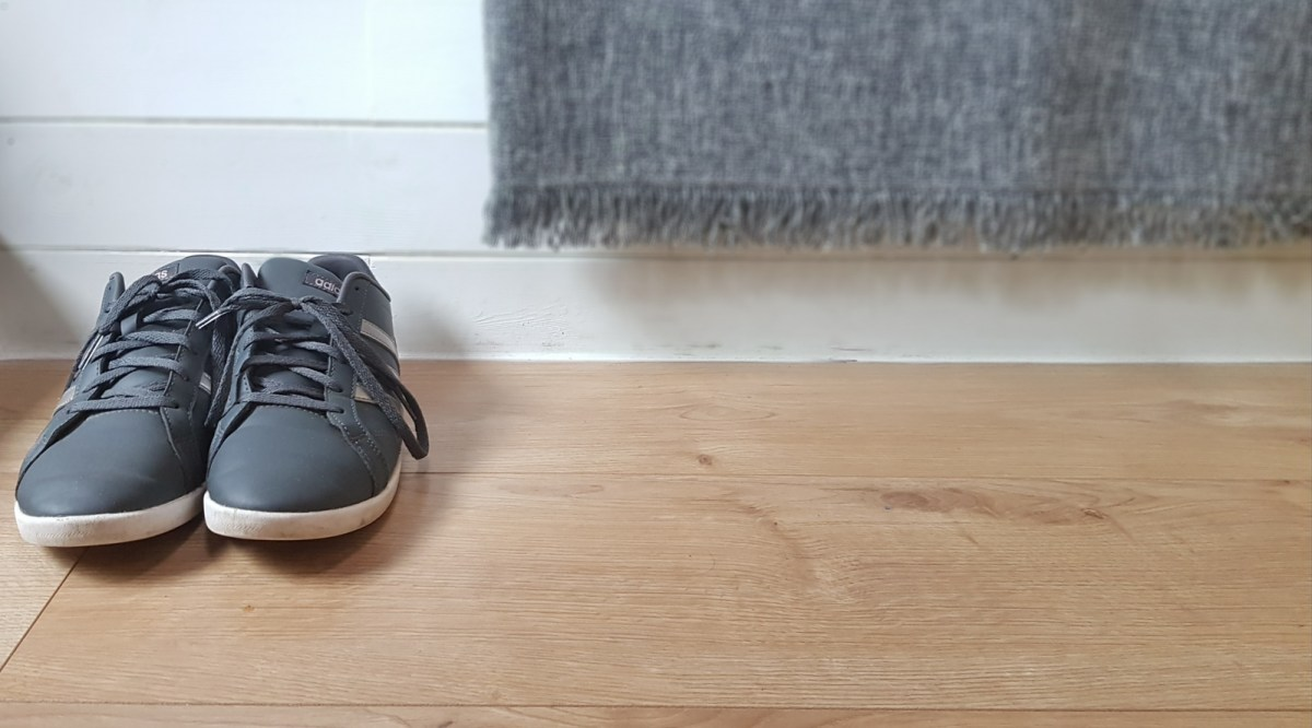 Grey Adidas trainers against a white wall decorated with a grey throw