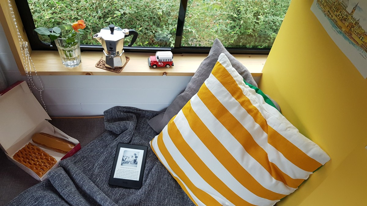 Decorative Campervan Accessories: a rose and coffee maker on snug's window sill + grey throw, stripy yellow & white pillow, a box of French patisserie & kindle reader