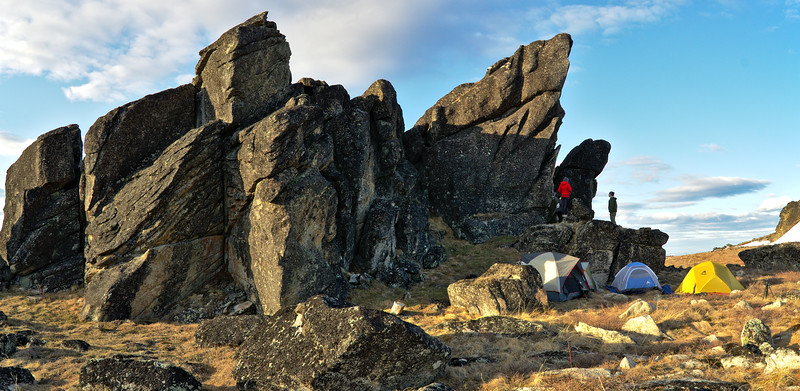Backcountry campsite and bacpackers under a granite tower at Granite Tors in Alaska