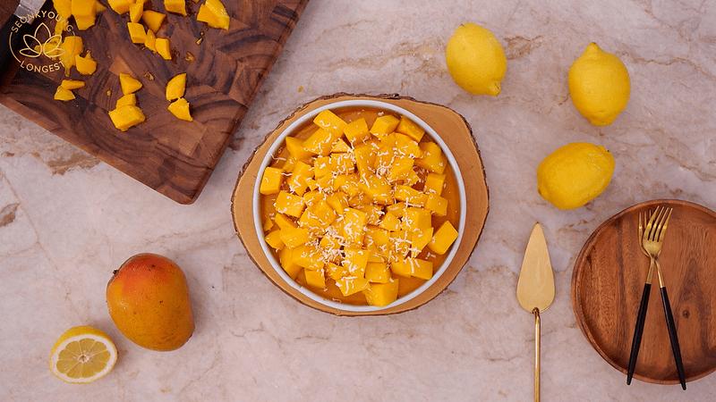 Plant-based Mango Cheesecake, garnish with extra mango chunks & coconut flakes