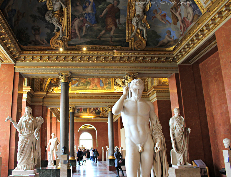 White sculptures against red walls and gold ceilings at the beautiful Louvre Museum