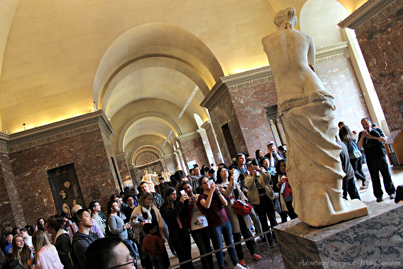 The Venus de Milo seen from behind, while crowds of visitors with cameras cluster to see her from the front