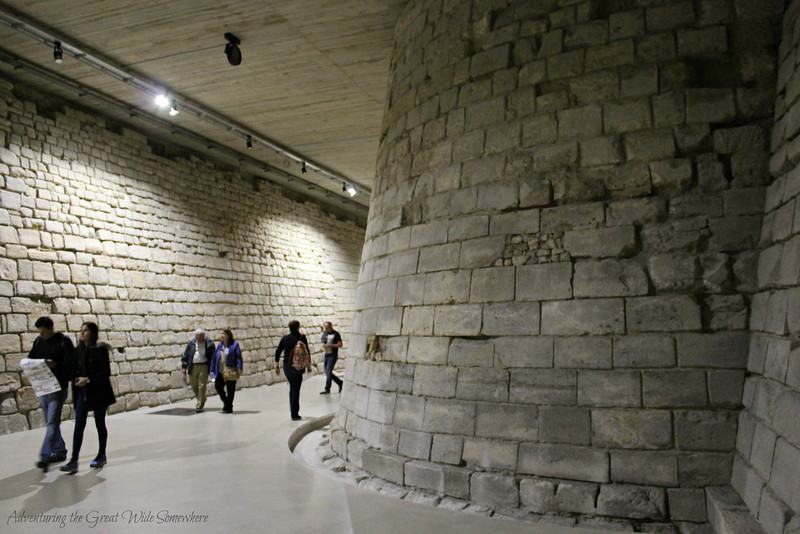 Visitors walking through the old moat of the Louvre Museum.