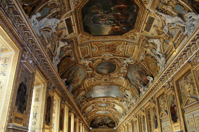 Full-room shot of the Apollo Gallery at the Louvre, covered in gold and beautiful painted details