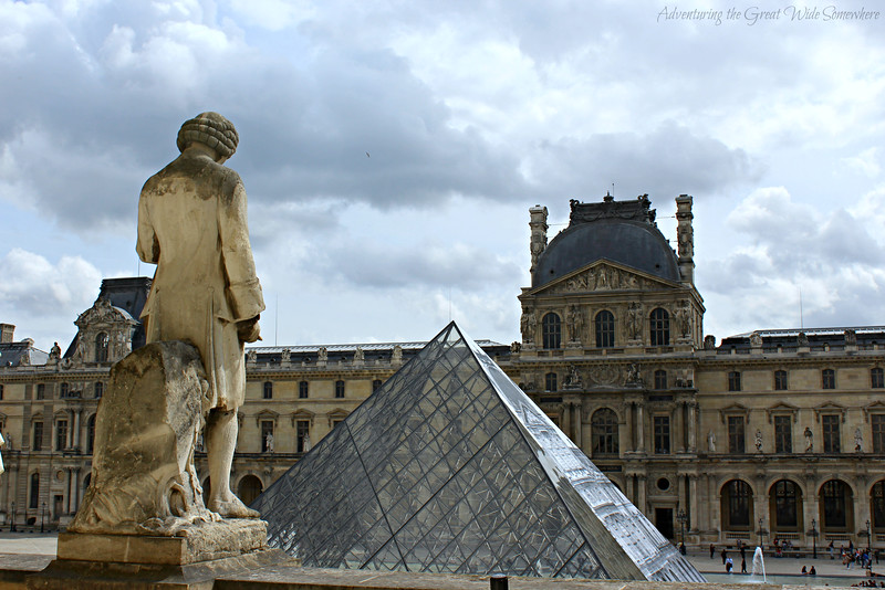 The view from one of the windows in the Louvre shows a statue gazing out over the famous glass pyramid.