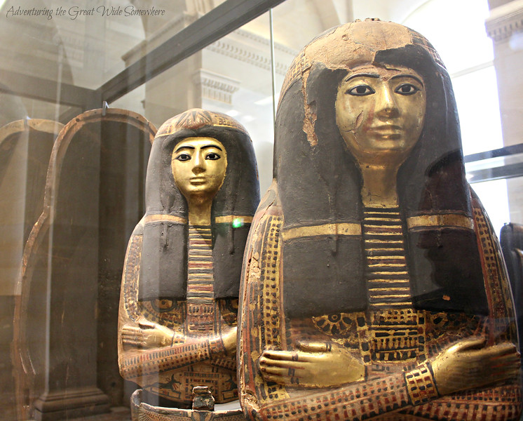 Two beautifully detailed sarcophagi, with crossed arms and golden faces, stands sentinel at the Louvre Museum