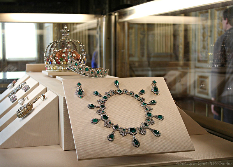 An emerald necklace, a crown, a tiara, and more crown jewels on display inside the Louvre's Apollo Gallery