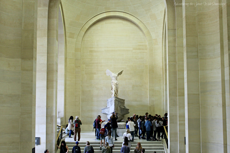 Winged Victory of Samothrace presides over a grand stone staircase, as museum-goers filter around on either side of the statue's base