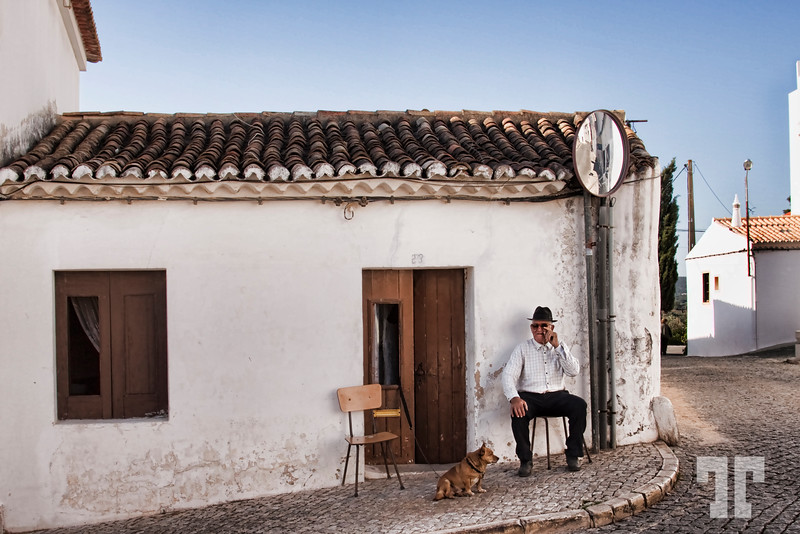 Old man and his dog in front of his house in Paderne, Portugal