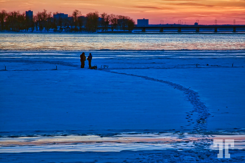 Ice fishing in the sunset Ottawa Canada - January