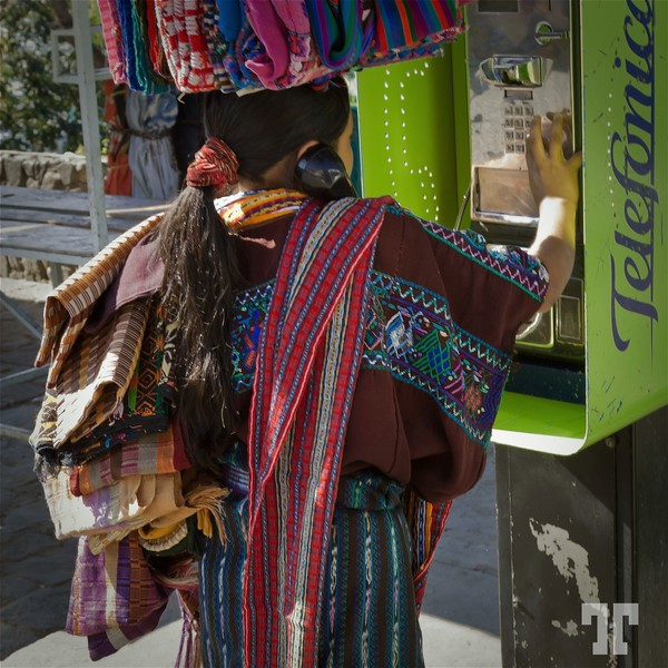 Indgenous craft vendor in Panajajel, Guatemala, making a phone call