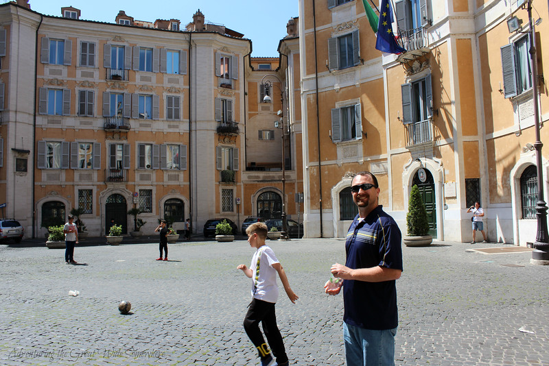 Children playing soccer in a piazza in Rome, Italy