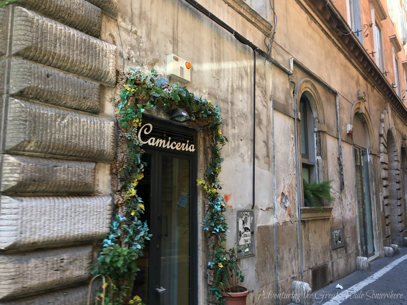 Shop entrance draped in ivy on the streets of Rome, Italy
