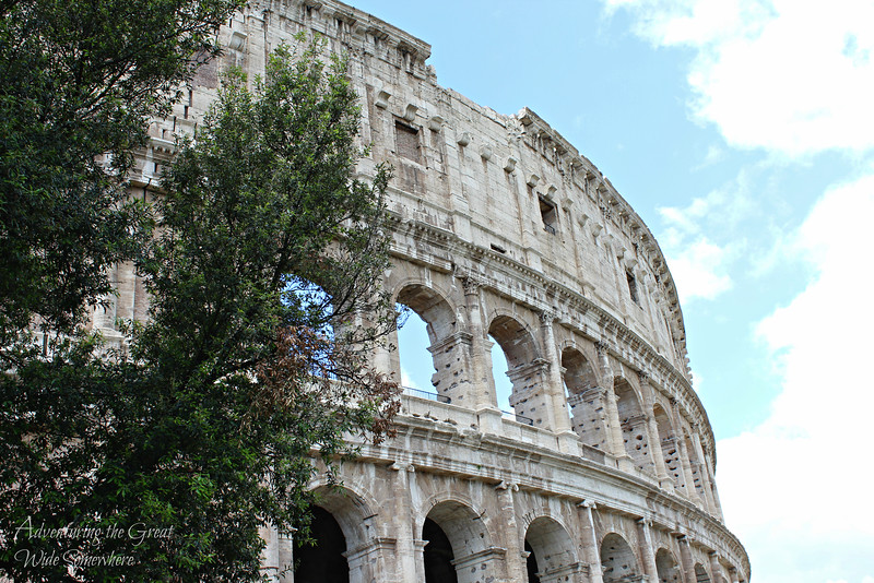 Exterior shot of the Colosseum, with beautiful blue skies in the background and lush green trees in the foreground.