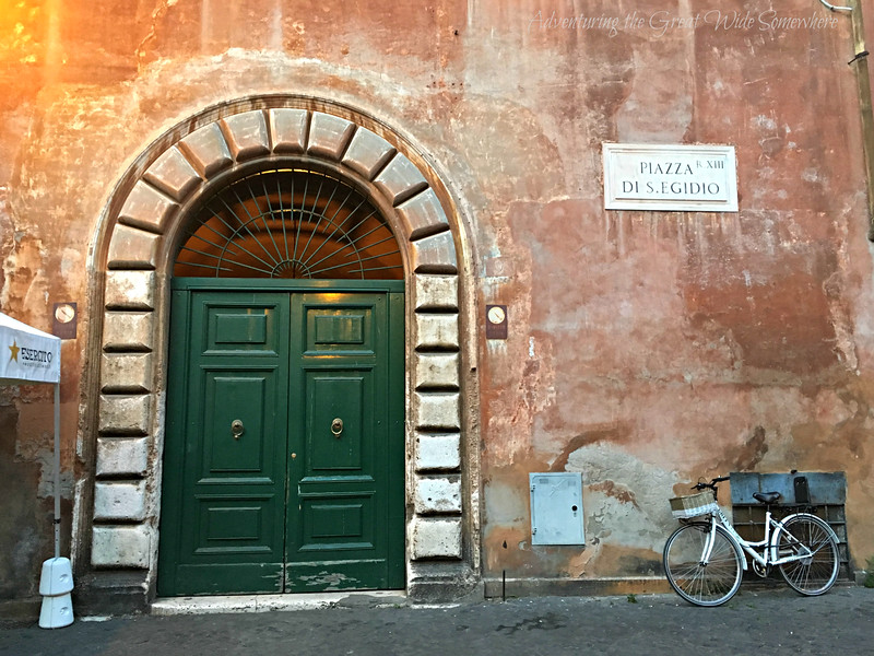 A beautiful green door and solitary bike in Piazza de S. Egidio, in the Travestere neighborhood of Rome, Italy.