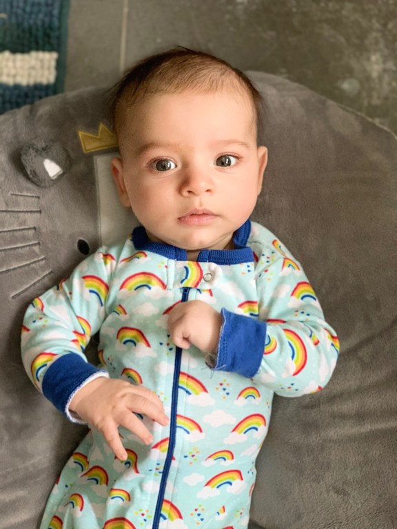 cute baby boy in rainbow leveret pajamas on boppy lounger