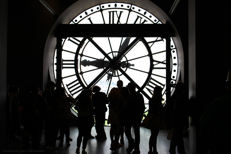 Museum-goers silhouetted in black and white behind the ornate clock face of the Musee d'Orsay in Paris.