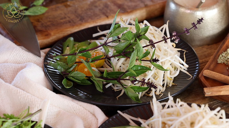 BEST Vegan Pho Recipe, beansprouts, chili, citrus and thai basil on a plate