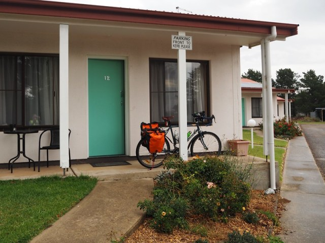 Bicycle with panniers leaning on a post outside a motel room