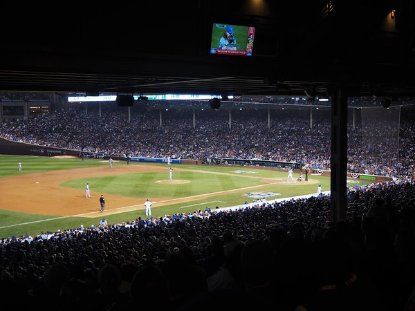 View of the field at Wrigley Field during a night game from a lower level seat, back in the crowd, along the right field line
