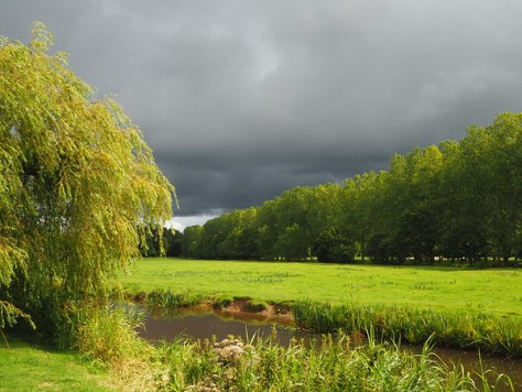 Heavy grey clouds blot the sky, but a small river courses through a sunlit green landscape.