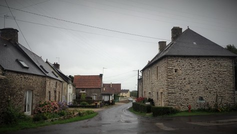 French stone village houses on a small wet street under a grey sky.