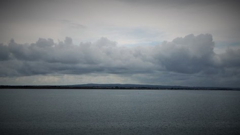 The gloaming: Low clouds over a gently rolling strip of Ireland on the horizon, the foreground calm steel-coloured sea.