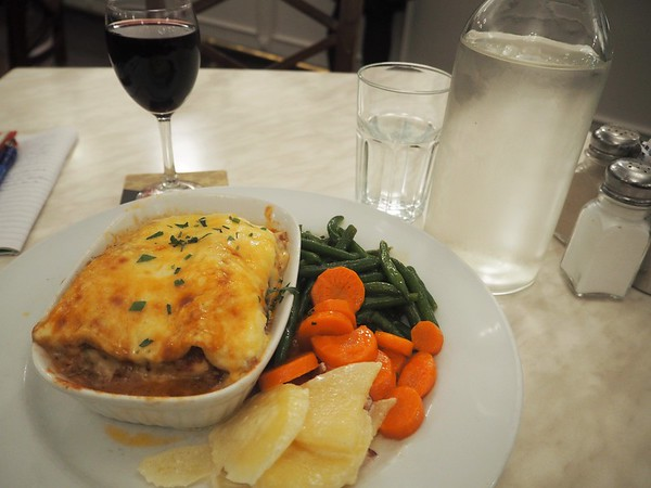Cheese-toped lasagne in a dish on a plate with a mound of green beans, carrots, and potatoes. Glass of red wine.