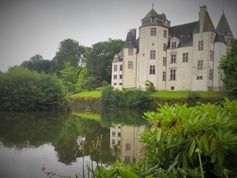 A white-stone French chateau reflected in a pond.