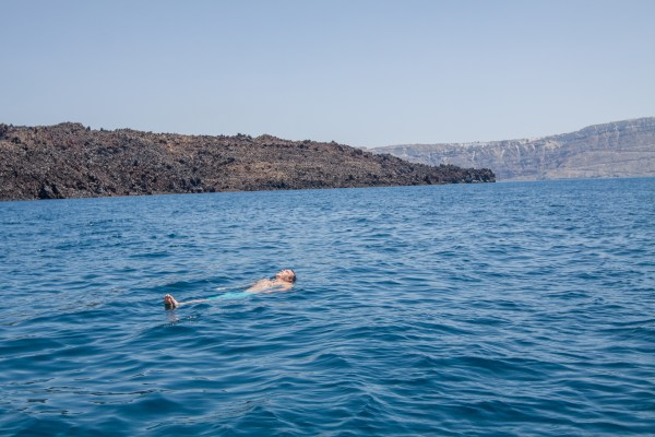 Santorini, Greece is famous for its cliffside towns and caldera views. While the birdseye view is fantastic, it's worth it to explore the island from the water as well! | www.eatworktravel.com