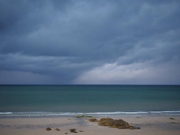 Rain heavy sky over a deep green to dark blue sea.