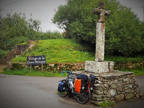 A fully-loaded touring bicycle leans against an age-wearied memorial cross in a small French village cross-roads, a signe reads: Village de la Croix Perrinot