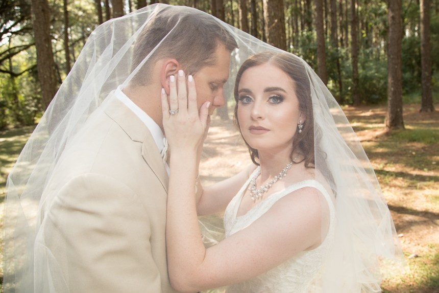 Photographed in September.  Intimate moment enclosed in bride's cathedral length veil.