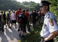 A Bosnian Serb policeman secures people during the second day of a four-day march to Srebrenica in the village of Liplje near Zvornik, 120 km (75 miles) north of Sarajevo Saturday, July 8, 2006. Hundreds of Bosnians began a four-day march on Friday along the route survivors used 11 years ago to escape the Bosnian Serb killings in Srebrenica, the worst massacre in Europe since World War II. (AP Photo/Amel Emric)