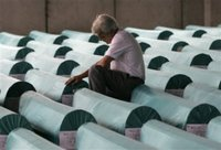 Bosniak (Bosnian Muslim) man cries near coffins of 505 newly identified Srebrenica victims at an abandoned battery factory in Potocari 120 kms north of Bosnian capital Sarajevo, Saturday, July 8, 2006. The bodies will be buried in Srebrenica on Tuesday during the 11th anniversary commemorations of the massacre. Serb troops killed some 8,000 Muslim men and boys at Srebrenica in 1995, and most of the bodies are still missing. (AP Photo/Amel Emric)