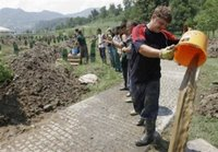 Bosnian workers removing water from the graves after the heavy rain hit the cemetery at the Memorial Center Potocari, near Srebrenica north of Bosnian capital Sarajevo, on Sunday, July 9, 2006. Newly identified bodies will be buried in Srebrenica on Tuesday (July 11th) during the 11th anniversary commemorations of the massacre. Serb troops killed over 8,000 Bosniak men and boys at Srebrenica in 1995. (AP Photo / Amel Emric)