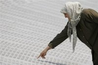 A Bosnian Muslim woman points to the name of her relative on the marble stone with 8,370 names of Srebrenica victims written on it, at the Memorial Center at Potocari, near Srebrenica north of the Bosnian capital Sarajevo, on Sunday July 9, 2006. The bodies of 505 newly identified Srebrenica victims will be buried in Srebrenica on Tuesday (July 11th) during the 11th anniversary commemorations of the massacre. Serb troops killed over 8,000 Bosniak men and boys at Srebrenica in 1995, and most of the bodies are still missing. (AP Photo/Amel Emric)