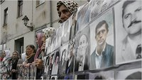 Bosnian women in Tuzla last week with photos of missing kin. They sought arrests of Bosnian Serb fugitives.